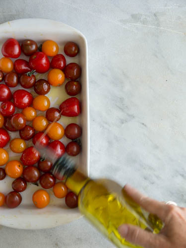 Oiling tomatoes for roasting- A Stack of Dishes